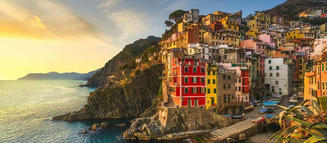 Riomaggiore town, cape and sea landscape at sunset. Seascape in Cinque Terre National Park, Liguria Italy Europe.
