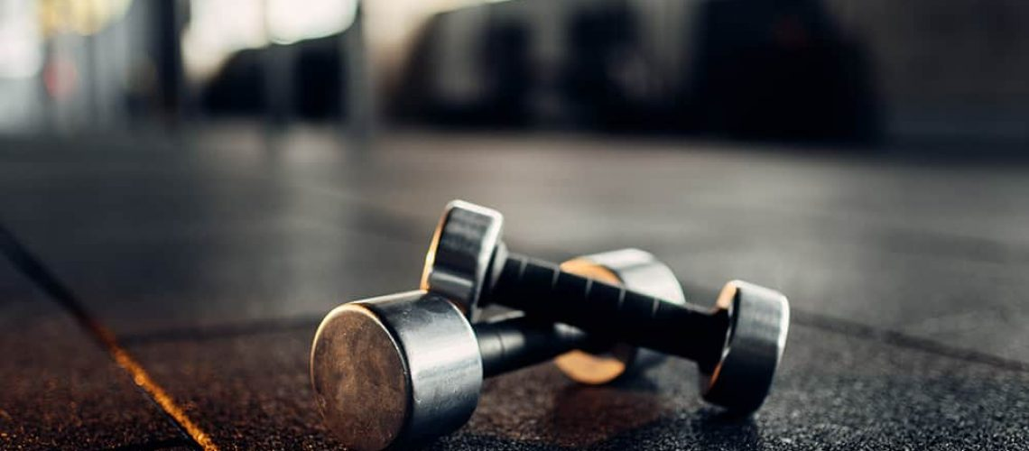 Dumbbells on rubber floor closeup view, fitness club, blur background