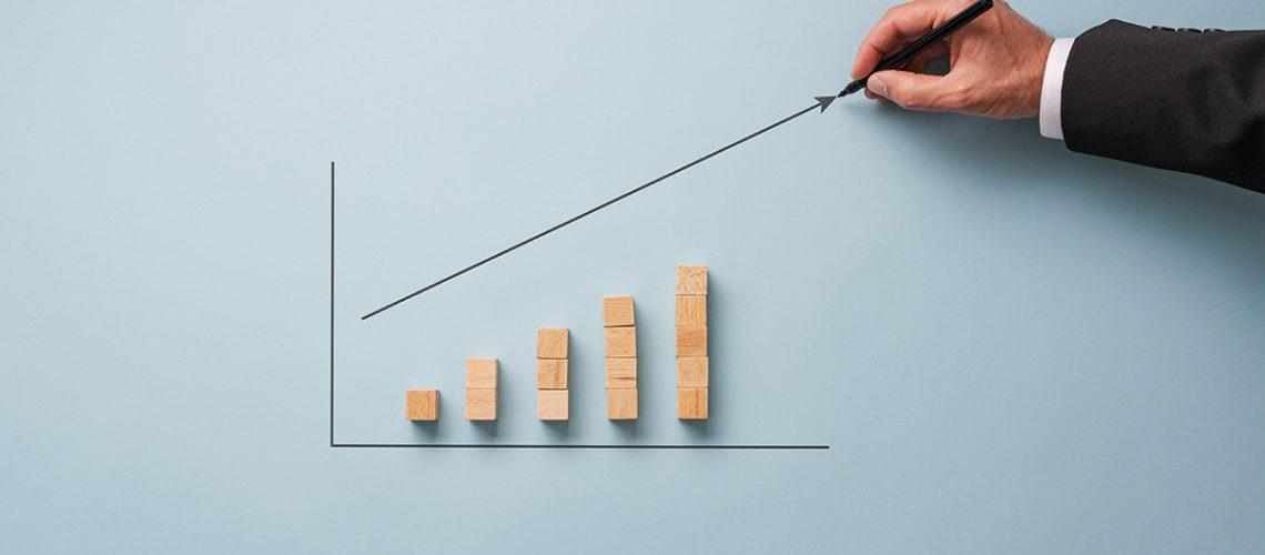 Hand of a businessman drawing a growing arrow above a column chart made of wooden blocks.